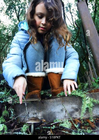 A young girl in a forest looking at a mushroom. - Stock Image