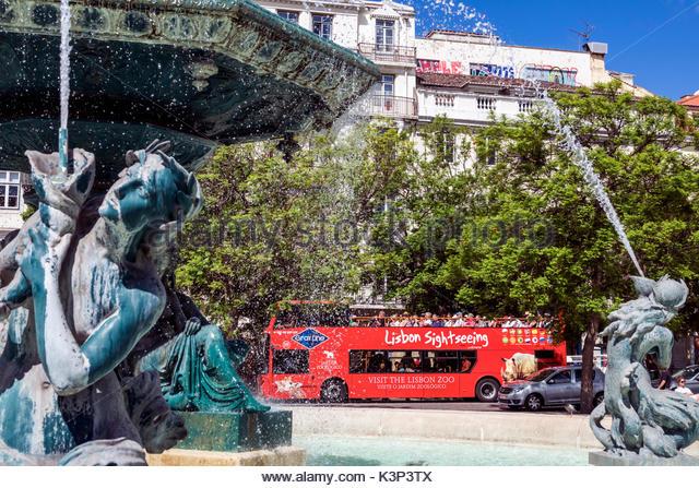 Lisbon Portugal Rossio Square Pedro IV Square fountain statue tour bus sightseeing double-decker motor coach - Stock Image