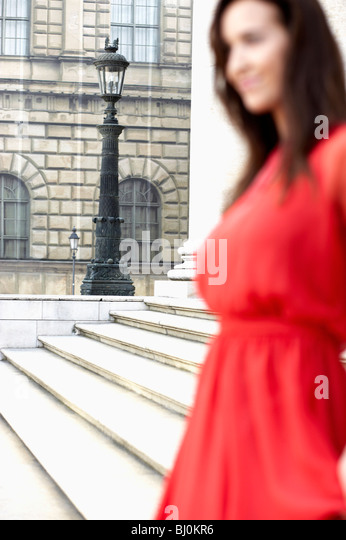 young woman in red dress standing in front of theatre - Stock Image