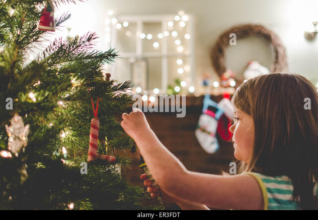 Girl decorating a Christmas tree - Stock Image