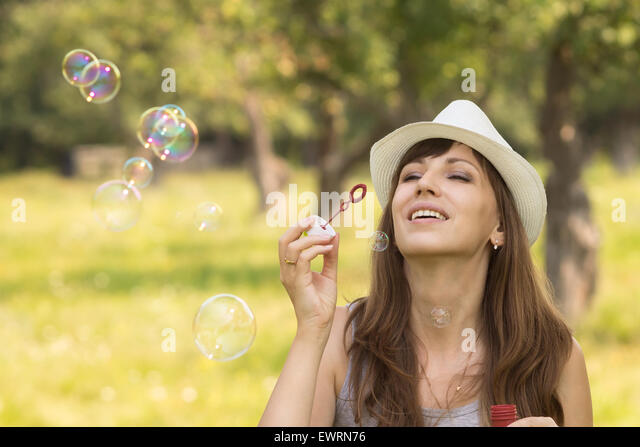 Young pretty caucasian woman having fun with blowing bubbles in summer park - Stock Image