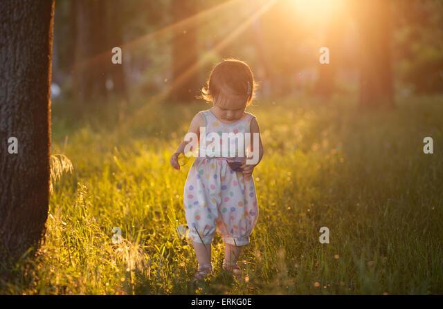 Walking baby in sunset lights - Stock Image