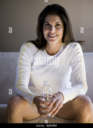 Woman sitting on sofa with bottled water - Stock Image