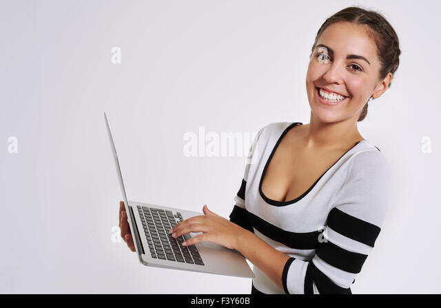 Happy smiling young woman using a handheld laptop computer to browse the internet looking at the camera with a warm - Stock Image