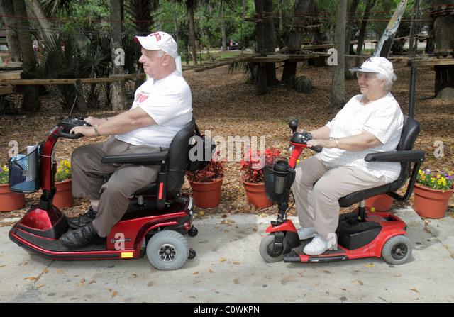 Orlando Florida Sanford Central Florida Zoo & and Botanical Gardens senior man woman disabled electric cart - Stock Image