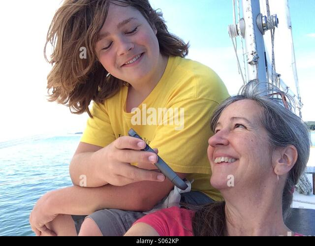 Teen and mom listening to iphone on boat - Stock Image