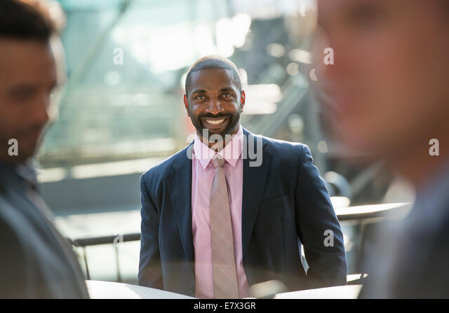 A business man seated smiling confidently, in a group with two others. - Stock Image