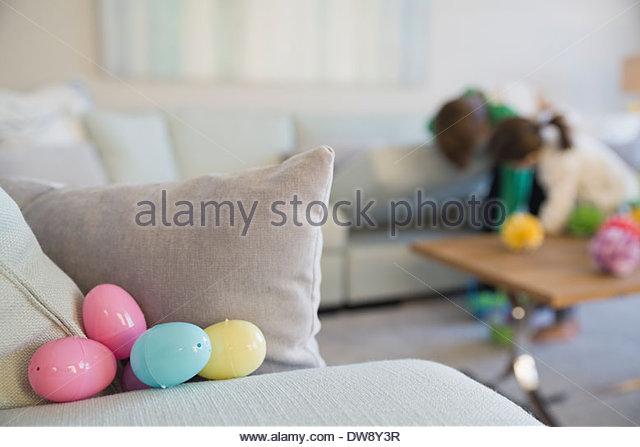Colorful Easter eggs behind cushion on sofa - Stock-Bilder