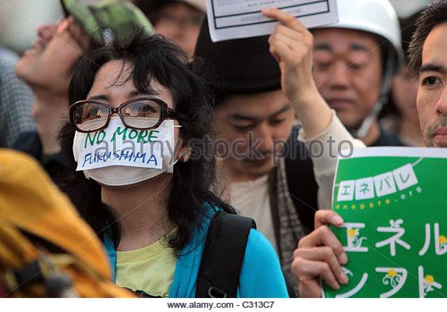 A protestor wears a 'No More Fukushima' mask, referring to the Fukushima Daiichi nuclear crisis in Japan. - Stock Image
