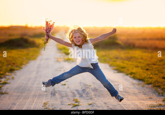 Young girl holding flowers jumping in air - Stock Image