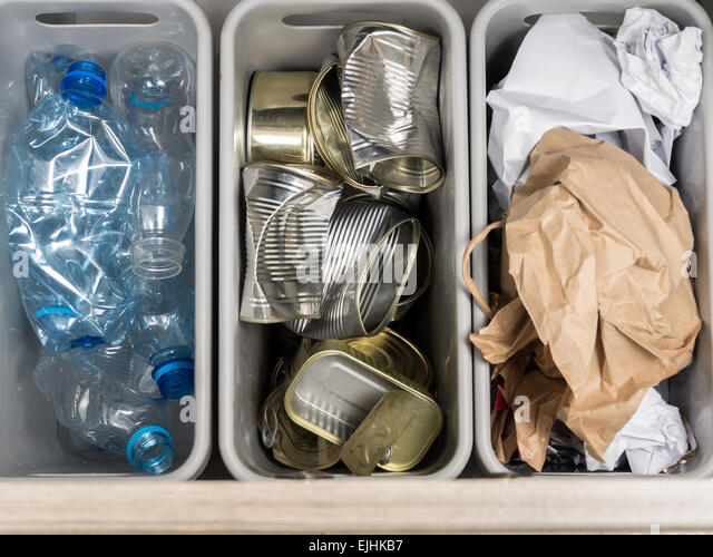 Three plastic trash bins with segregated household garbage - PET bottles, paper and metal cans shot from above - Stock Image