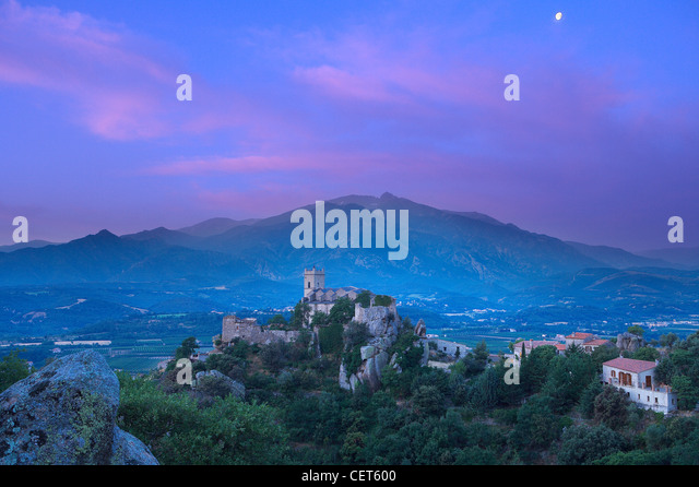 the village of Eus perched on a hilltop with the Pic de Canigou beyond, the Pyrenees, Languedoc-Rousillon, France. - Stock-Bilder