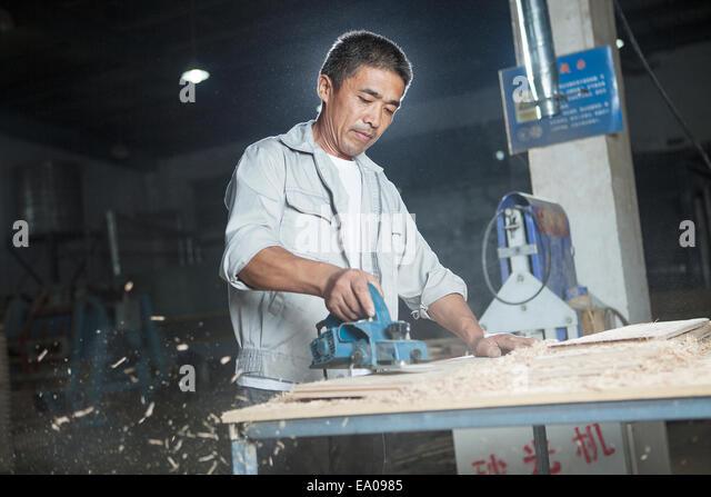 Carpenter cutting wood plank in factory, Jiangsu, China - Stock Image