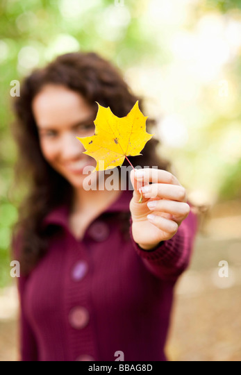 young woman shows leaf - Stock Image