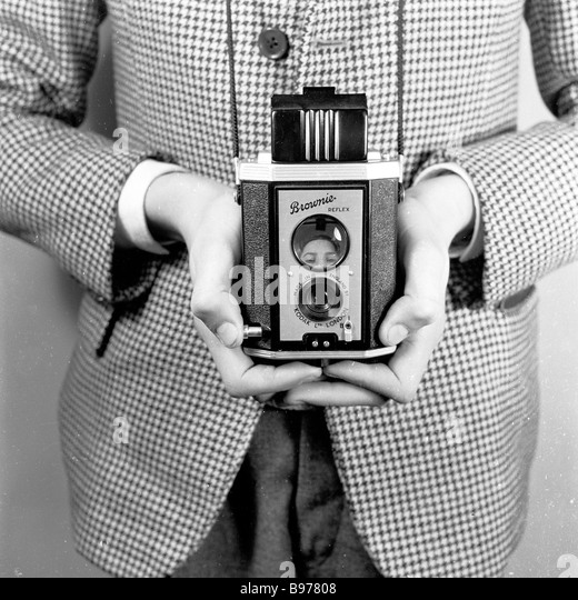 Young boy demonstrating how to hold a Kodak 'Brownie' twin-lens reflex box photographic film camera, England, - Stock Image