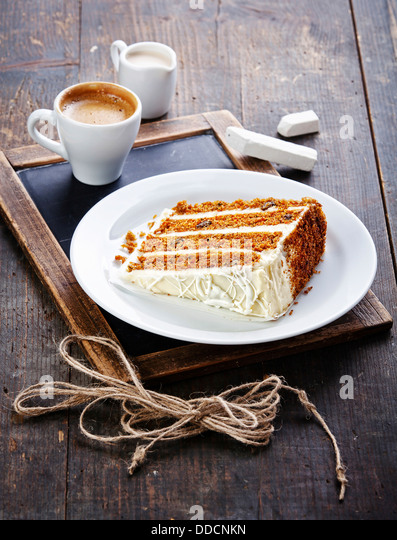 Slice of carrot cake on vintage slate chalk board background - Stock Image