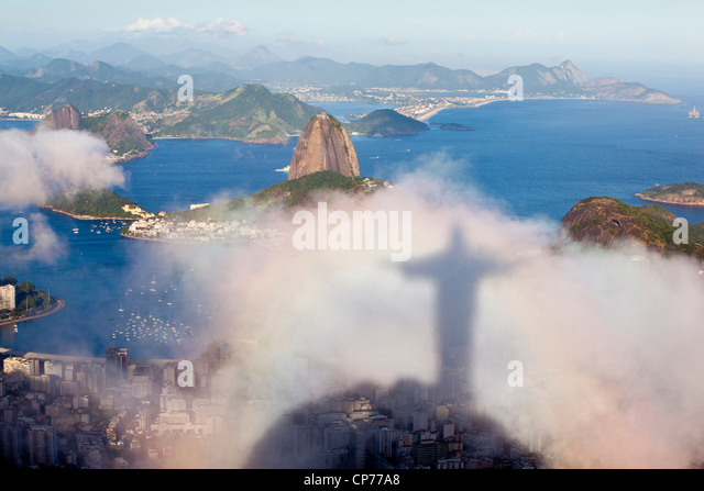 Shadow of Christ the Redeemer statue projected on cloud, Sugar Loaf and Niteroi city beaches on background Rio de - Stock-Bilder