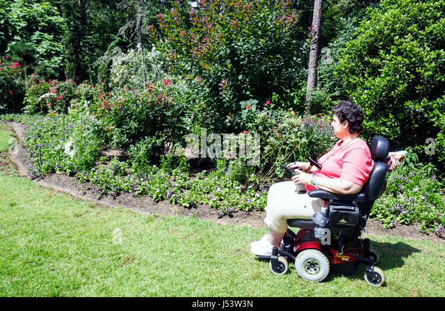 Arkansas Hot Springs Garvan Woodland Gardens woman visitor disabled physically impaired accessible electric wheelchair - Stock Image