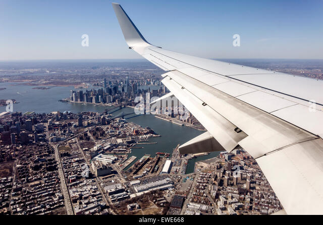 New York City NY NYC Manhattan Brooklyn aerial American Airlines commercial airliner plane flight window seat view - Stock Image