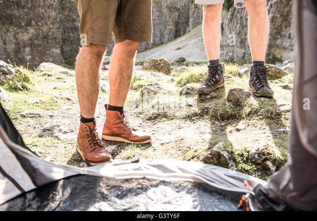 The legs of two men viewed from inside their tent in rugged terrain. - Stock Image