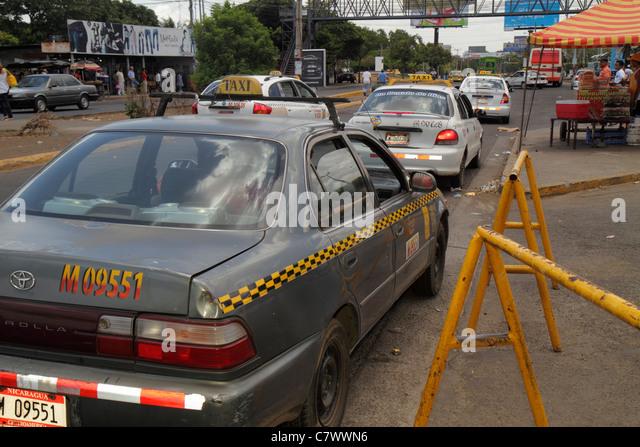 Nicaragua Managua Metrocentro business district street scene traffic car taxi stop cab checkered stripe trash transportation - Stock Image