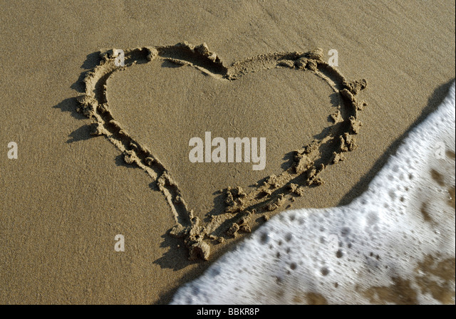 Symbol of a heart drawn in the sand - Stock Image