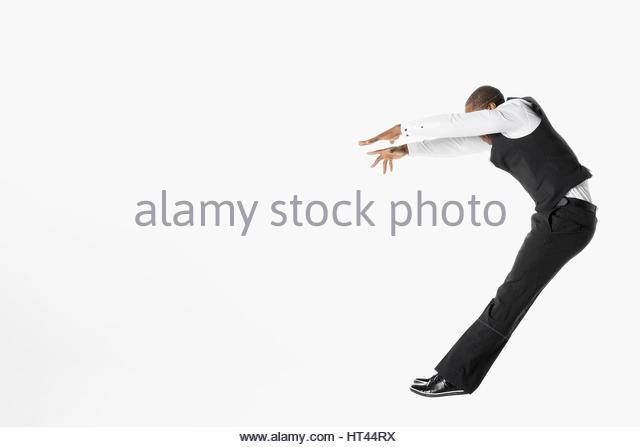 Businessman jumping, falling back against white background - Stock-Bilder