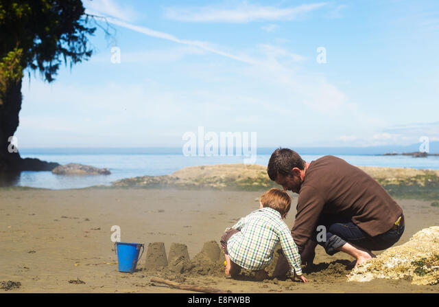 Father and son ( 2-3 ) building sandcastle - Stock-Bilder
