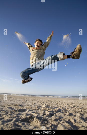 boy,sea,jump,vitality,ecstatic - Stock Image