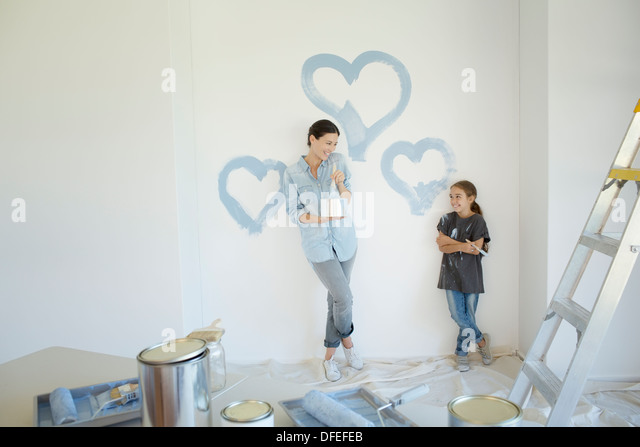 Mother and daughter painting blue hearts on wall - Stock Image