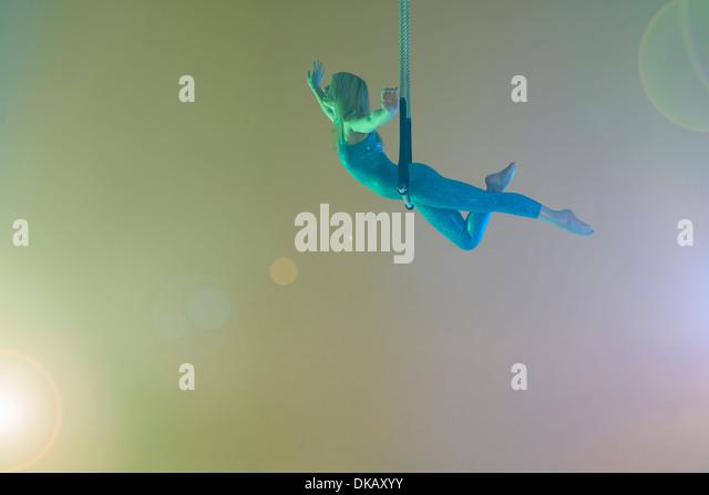 Trapeze artist balancing on trapeze - Stock Image