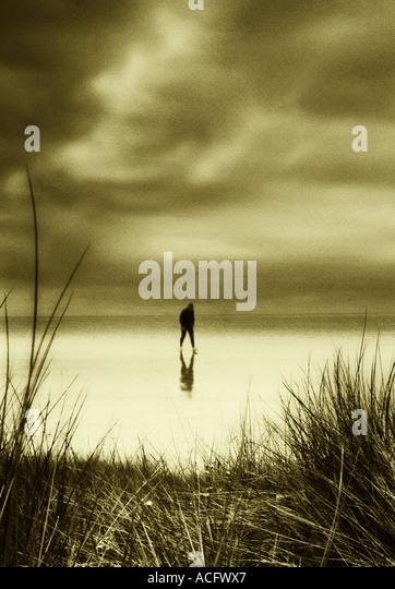 Photo of a man walking along a sandy beach alone - Stock Image