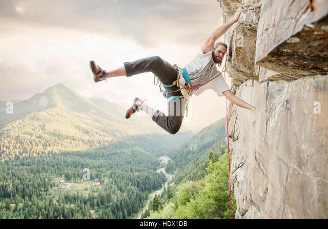 Caucasian man hanging from rock while climbing - Stock Image