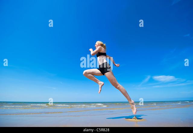 An jogger running along a beach - Stock Image