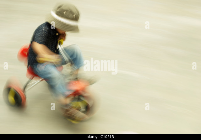 Boy on tricycle - Stock Image