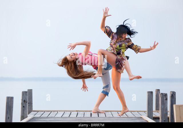 two girl  are dancing on background of water and sky - Stock-Bilder