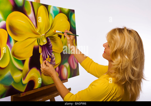 A female artist painting dendrobium orchids on canvas in her studio - Stock Image