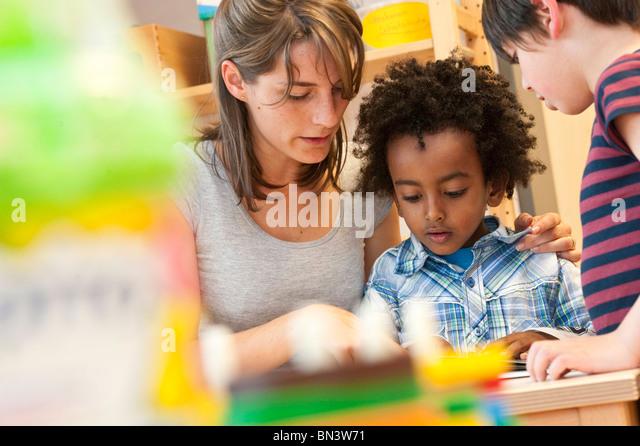 Kindergarten teacher reading children, low angle view - Stock Image
