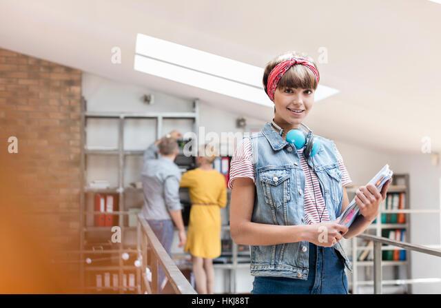 Portrait smiling female design professional with headphones in office - Stock-Bilder