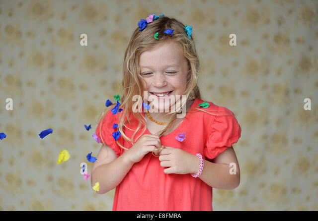 Portrait of a girl covered in confetti laughing - Stock Image