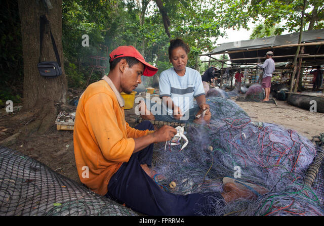 Thai fishermen mending their nets - Stock Image