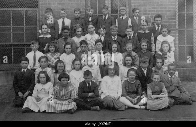 Full length landscape shot of schoolchildren, seated and standing outdoors, some African American, 1920. - Stock Image