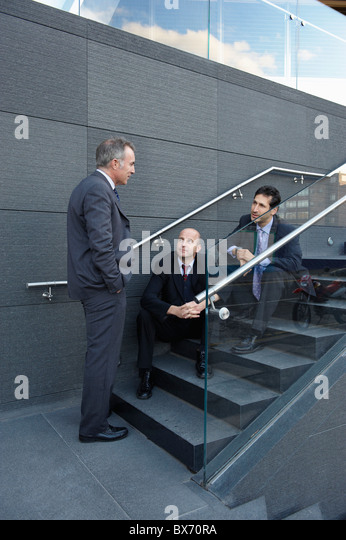 Business colleagues sitting on stairs having a chat - Stock Image