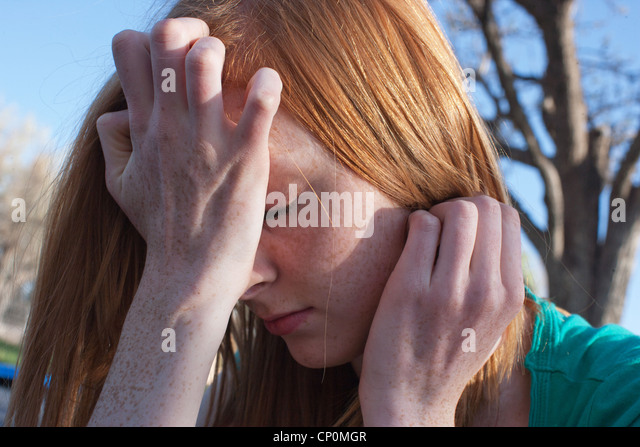 Close of a sixteen year old girl experiencing anxiety and covering her face with her hands outdoors. - Stock-Bilder
