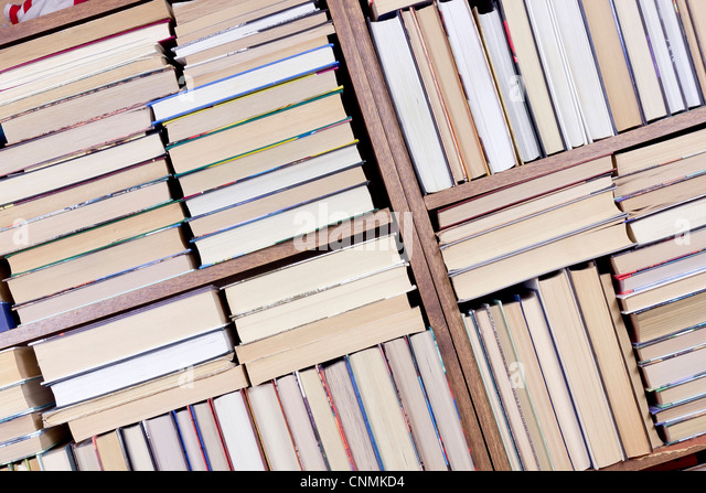 Old retro books on a wooden shelf front view. Mass production, selective focus. - Stock Image