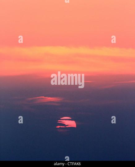 Beautiful colorful sunset behind tes clouds, Santorini, Greece - Stock Image