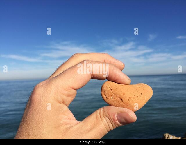 Love message conceptual image with a stone heart between fingers - Stock Image