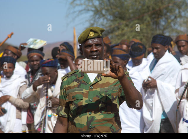 Soldier filming with his mobile phone during the Gada system ceremony in Borana tribe, Oromia, Yabelo, Ethiopia - Stock-Bilder