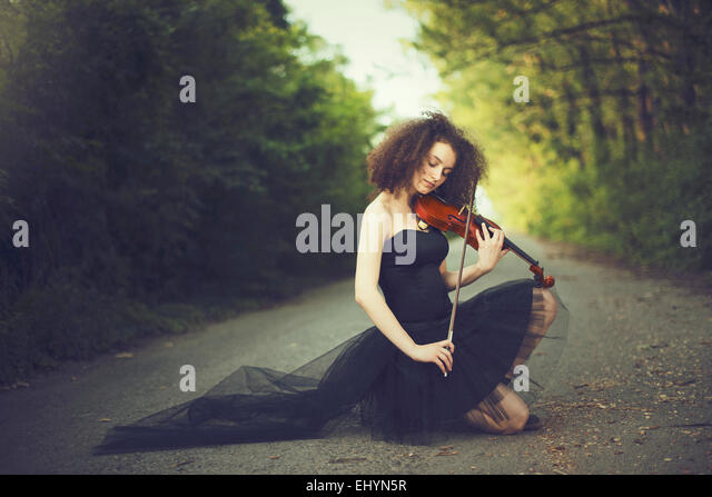 Sad young woman playing the violin - Stock Image