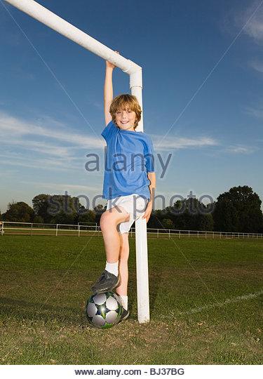 Boy with ball leaning against goal post - Stock Image
